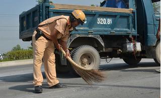 Cảnh sát giao thông TP.HCM hì hục đội nắng, quét dọn đá dăm trên đường