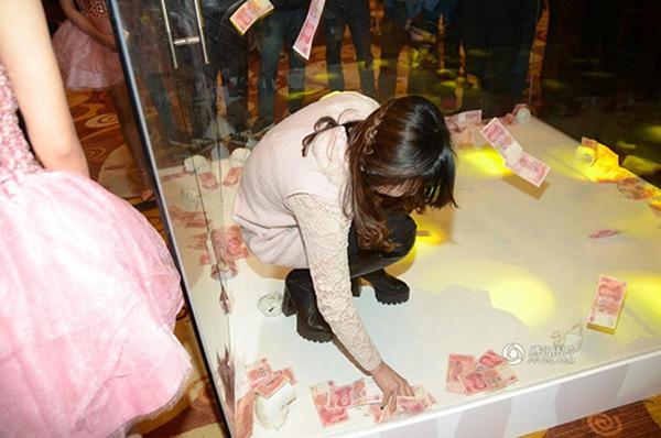 Sức lực có hạn, nhân viên nữ dùng tay nhặt tiền cho nhanh. Ảnh: QQ
