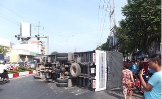 Xe tải ôm cua bị lật giữa đường, một người phụ nữ thoát chết trong gang tấc