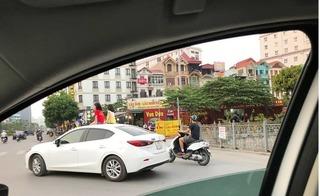 Bé gái ngồi vắt vẻo trên nóc ô tô đang chạy ở Hà Nội