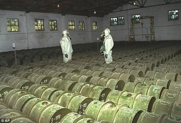 Hai binh sĩ Nga kiểm tra các thùng kim loại chứa chất độc hóa học. Ảnh: AP