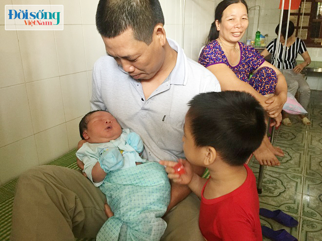 Bố cháu bé cùng con trai cả vui mừng bên cậu út vừa sinh