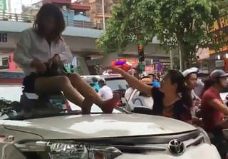Bị phạt vì vượt đèn đỏ, nữ tài xế trèo lên nóc xe