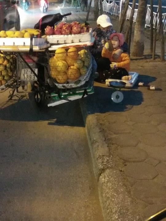 Cô bé theo mẹ bán hoa quả ngoài đường giữa chiều đông giá lạnh