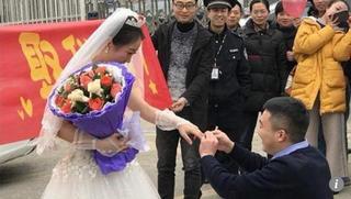 Cô gái xinh đẹp mặc váy cưới chủ động cầu hôn bạn trai ngay cửa nhà tù