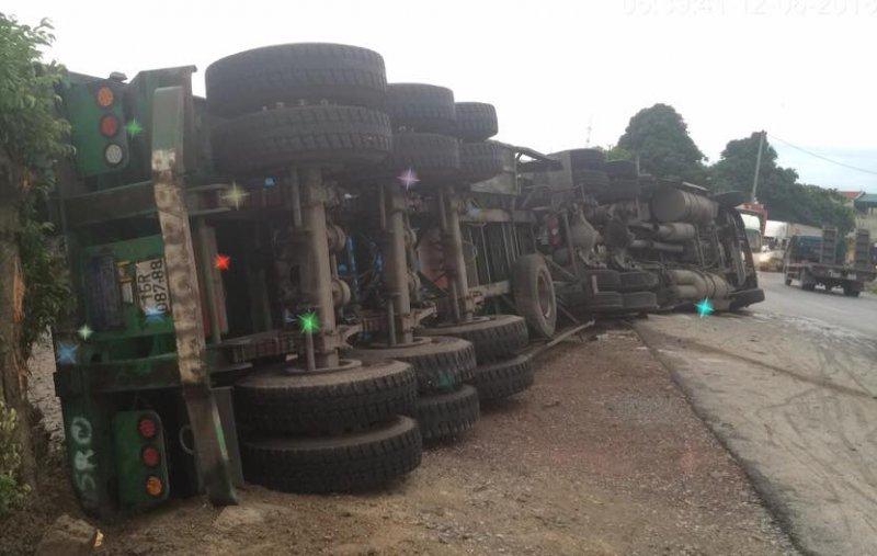 Va chạm với xe tải lúc ôm cua, xe container lật nhào giữa đường