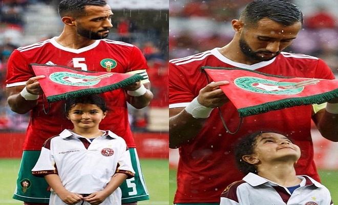Ấm áp khoảnh khắc đội trưởng tuyển Morocco dùng cờ hiệu che mưa cho bé gái trên sân cỏ