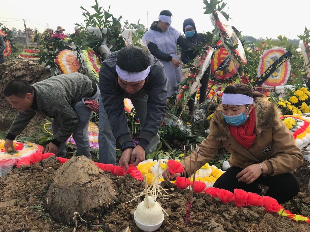 Người thân của các nạn nhân ngồi gắn hoa nhựa lên ngôi mộ