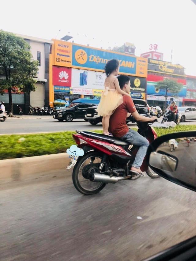 Người đàn ông để bé gái đứng sau yên xe rồi phóng tít mù trên đường