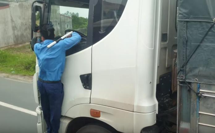 Thanh tra giao thông đu người trên đầu xe tải yêu cầu tài xế vượt trạm cân dừng xe