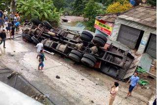 Xe tải lật ngửa khi đang đổ dốc trên quốc lộ, 2 bố con tài xế thương vong