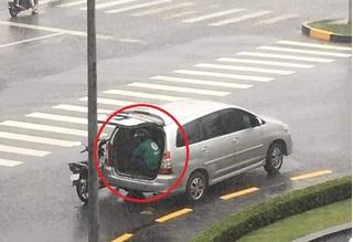 Ô tô 7 chỗ mở cốp để tài xế Grab ngồi trú mưa khiến nhiều người ấm lòng