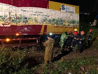 Nỗ lực đưa thi thể dưới gầm xe container ra ngoài trong đêm mưa