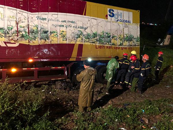Hàng chục cảnh sát nỗ lực đưa thi thể dưới gầm xe container ra ngoài trong đêm mưa