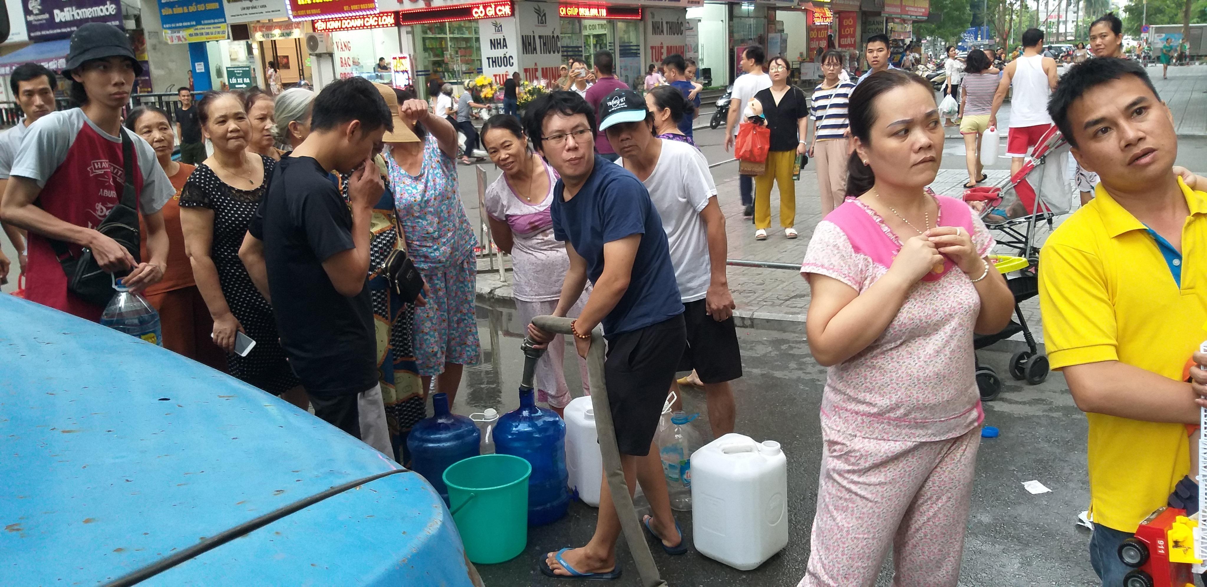 Hàng trăm cư dân Linh Đàm xếp hàng nhận nước sạch, chờ kết quả xét nghiệm