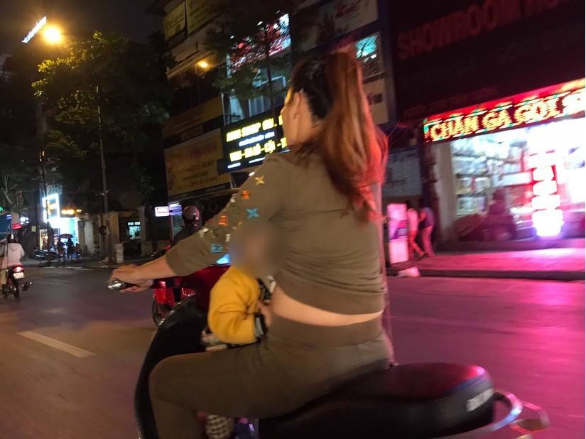 Sốc với cảnh người mẹ vừa lái xe máy vừa cho con trai bú trên đường3