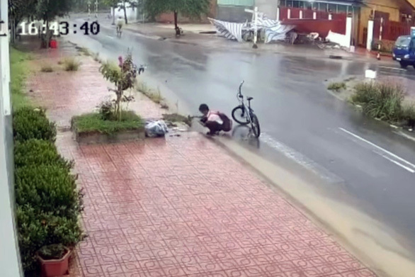 Đồng Nai: Nam sinh nhặt rác trên miệng cống giữa trời mưa