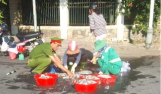 Xúc động hình ảnh anh công an và chị lao công giúp dân nhặt mẻ cá đổ ra đường