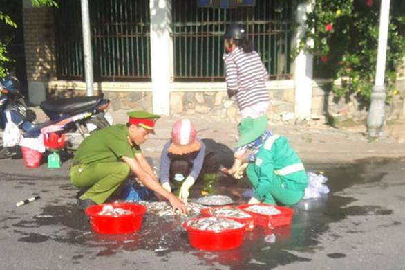 Xúc động hình ảnh công an và lao công giúp dân nhặt mẻ cá văng ở đường