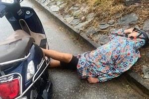 Người đàn ông say rượu dựng xe giữa đường, gối đầu lên vỉa hè ngủ