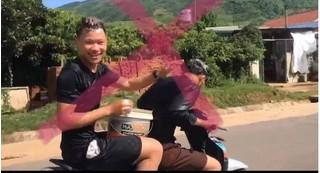 2 thanh niên vừa đi xe máy vừa múc nước gội đầu trên quốc lộ