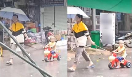 Thản nhiên che ô mặc em bé dầm mưa tầm tã, người phụ nữ bị chỉ trích vô cảm