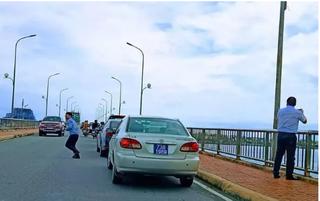 Tài xế xe biển xanh dừng trên cầu Nhật Lệ chụp ảnh bỏ tiền túi nộp phạt