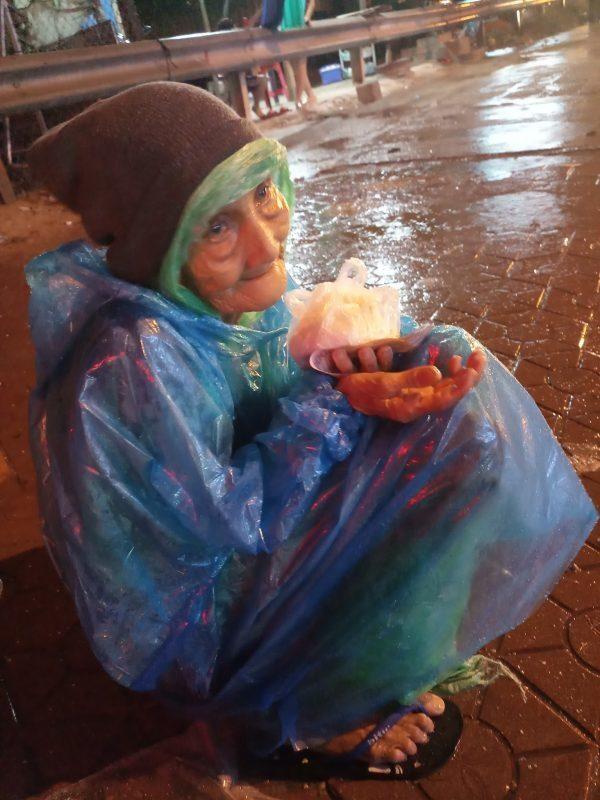 Cụ bà cầm chiếc bánh bao được tặng cẩn thận trên tay để đem về cho chồng.