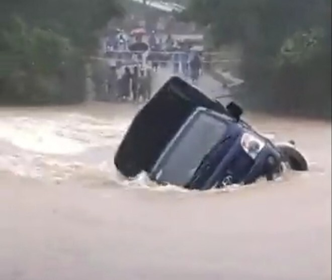 Chạy đến giữa cầu thì chết máy, xe tải bị dòng nước lũ cuốn trôi