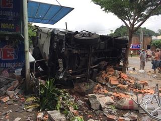 Xe tải hất tung tung xe máy khi ôm cua rồi lật vào nhà dân
