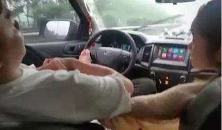 Tài xế ngả lưng ghế, dùng chân điều khiển ô tô, tay thì 'âu yếm' bạn gái ngồi bên cạnh