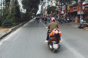 Hình ảnh bé gái ngủ gục, nằm hẳn ra yên xe máy trên phố Hà Nội khiến ai cũng phải thót tim